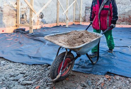 Worker in protect gloves is hauling the building trolley with sand to making the concrete in construction site. Concept of using of construction materials during construction, remodeling, renovation, extension, overhaul, restoration and reconstruction