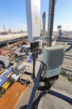 Russia, Saint-Petersburg - April 30, 2018: Outdoor remote radio unit (RRU) and cables of Base Transceiver Station (BTS) are installed on top of a building. Outside part 5G, 4G, 3G, 2G basic station.