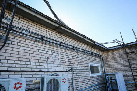 Russia, Saint-Petersburg - April 30, 2018: Metal ladder trays with power, data, optic and ground cables of Base Transceiver Station (BTS) are installed on top of a building. Outside part 5G, 4G, 3G, 2G basic station 에디토리얼