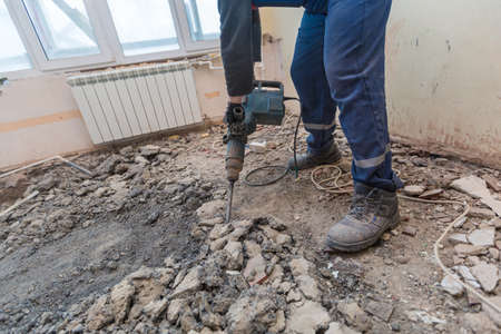 Working process of dismantling and disassembling the floor with construction electric perforator in room of apartment is that under construction, remodeling, renovation, extension, restoration and reconstruction