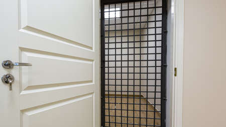 The white door with grid that is as prison cell. Concept of house arrest.