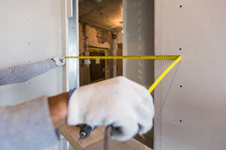 Worker measures distance in doorway after installing drywall in apartment that is under construction
