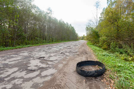 Destroyed rubber car tire car on rural bumpy broken road 免版税图像