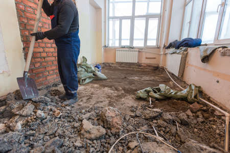 Working process of cleaning with shovel after dismantling and disassembling the floor in room of apartment is that under construction, remodeling, renovation, extension, restoration and reconstruction