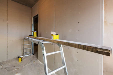 Working process of installing metal frames for plasterboard -drywall - for making gypsum walls in apartment is under construction, remodeling, renovation, extension, restoration and reconstruction. 免版税图像