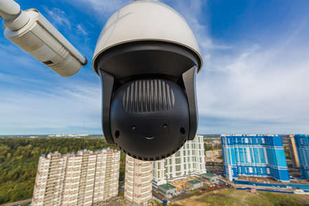 CCTV surveillance cameras installed on modern building. Video equipment outdoor safety system area control. Security camera on the roof. 스톡 콘텐츠