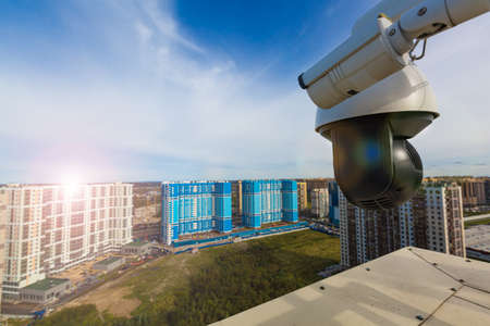 CCTV surveillance cameras installed on modern building. Video equipment outdoor safety system area control. Security camera on the roof. 免版税图像