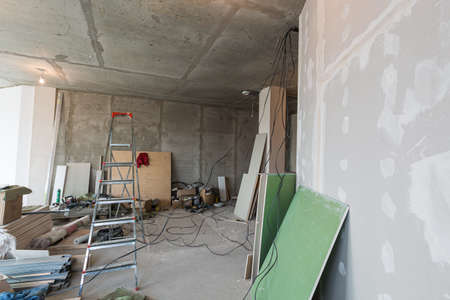 Working process of renovate room with installing drywall or gypsum plasterboard and ladder with construction materials are in apartment is under construction, remodeling, renovation, extension, restoration and reconstruction. Concept of home improvement or renovate. 스톡 콘텐츠