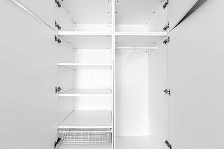 New empty closet wardrobe shelves by white finish wooden material and opened doors. Closet with hangers and rail rack in white bedroom.