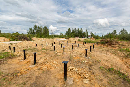 Iron screw piles in the ground for a new building on construction site.