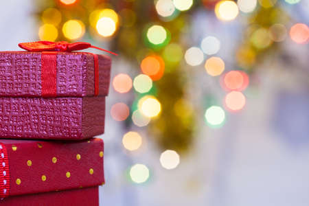 Boxes with christmas gifts with red bow and christmas bokeh light abstract holiday background