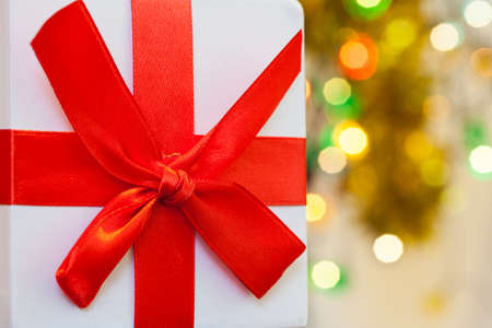 Box with christmas gift with red bow and christmas bokeh light abstract holiday background. 免版税图像