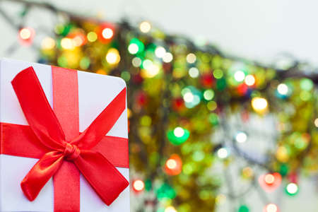 Box with christmas gift with red bow and christmas bokeh light abstract holiday background 免版税图像
