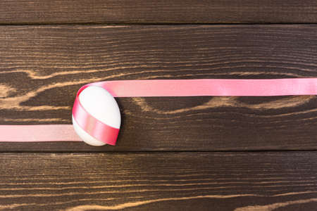 Easter egg is tied pink ribbon on the wooden background 免版税图像