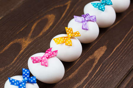 Line of easter eggs with colorful bows are on the wooden background. 免版税图像
