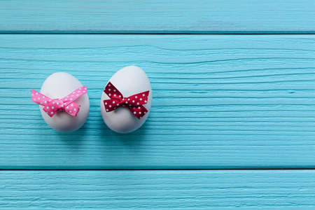Easter eggs with white spotted bow on the red and pink colored wooden background.