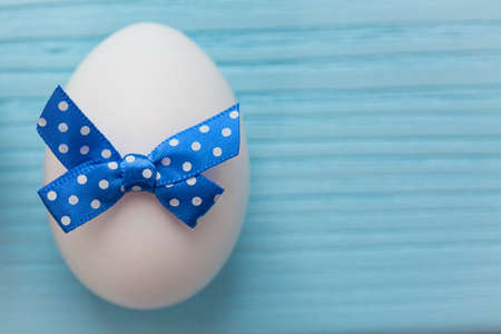 Blue colored Easter egg with white spotted is on the wooden background.