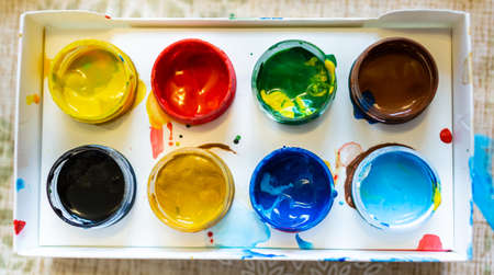 Top view of the bright colorful paints in paper box, close up