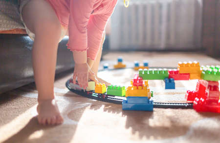 Toddler child girl in a diaper plays in room with train toy. 免版税图像