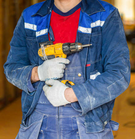 Worker in dirty uniform and protective gloves with drill in his hand in the room of apartment that is under construction, remodeling, renovation, extension, overhaul, restoration and reconstruction.