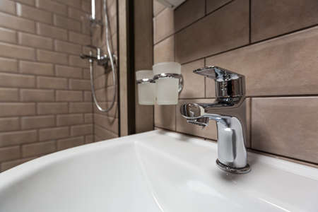 Water tap, faucet in the bathroom with sink. Hygiene concept.