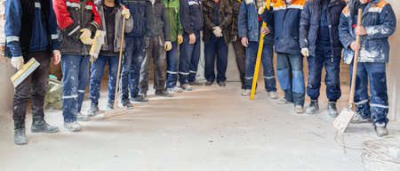 Workers and builders and foreman are as gang with dirty uniform are staying in apartment that is under construction, remodeling,renovation,extension, restoration, overhaul and reconstruction 免版税图像