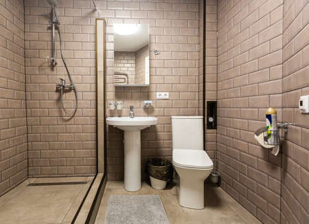 Bathroom covered brown tiled, mirror and sanitary engineering is in the apartment that is afer construction, remodeling, renovation, overhaul, extension, restoration and reconstruction. Concept of home improvement