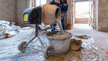 Worker is using the electric concrete mixer in an apartment is under construction, remodeling, renovation, extension, restoration and reconstruction.
