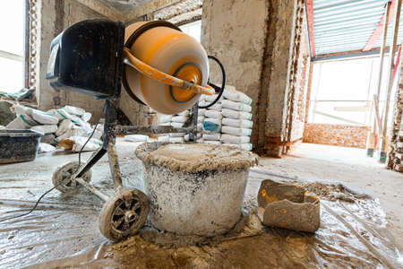 The using the electric concrete mixer in an apartment is under construction, remodeling, renovation, extension, restoration and reconstruction
