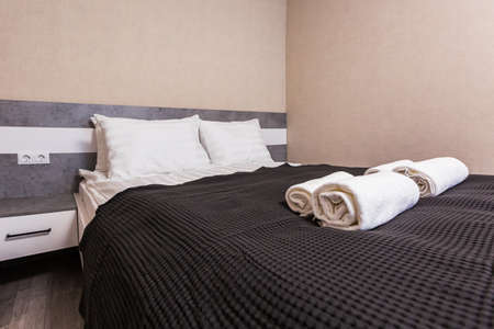 Two white towels and two striped pillows are on the bed in hotel room. Stack of towels on a hotel bed.