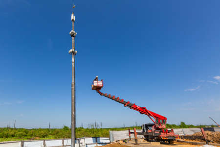 Engineer starts working on the telecommunication tower -cellular phone repeater mast - from An aerial work platform, also known as an aerial device, elevating work platform, cherry picker, bucket truck, mobile elevating work platform