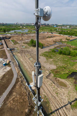 Telecommunication tower with microwave equipment 5G, radio panel antennas, outdoor remote radio units, power cables, coaxial cables, optic fibers, climatic vandal-proof cabinets  are installed on the mast 免版税图像