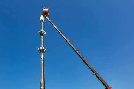 Engineer is working on the telecommunication tower - cellular phone repeater mast - from An aerial work platform, also known as an aerial device, elevating work platform, cherry picker, bucket truck, mobile elevating work platform