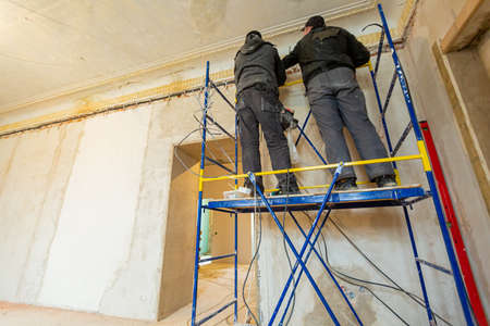 Two workers is installing the electrical wires on the wall that is the part of internal wiring in apartment that is under construction, remodeling, renovation, extension, restoration and reconstruction