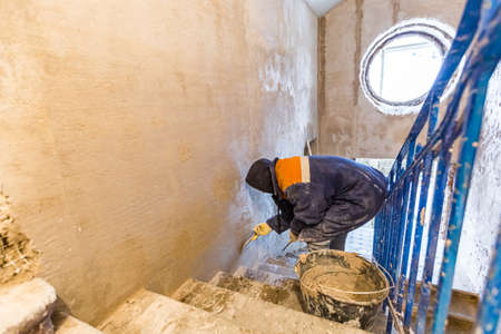 Worker is cementing by the putty knife the wall in room that is under construction, remodeling, renovation, extension, restoration and reconstruction.