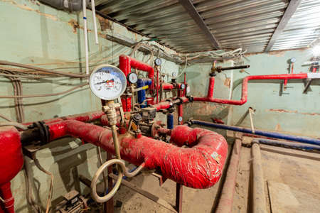 Manometer of center plumbing system and valves, stainless ball valves, detectors of water pressure and plastic and steel pipes of central heating system and water pipes with red thermal insulation in the boiler room. Concept of old independent private furnace room or heat boiler station 免版税图像
