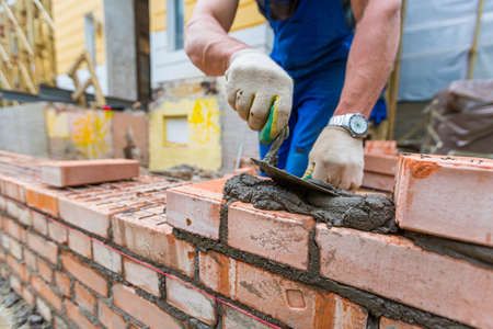 Bricklayer is laying brickwork on exterior wall with putty knife in construction site. 免版税图像