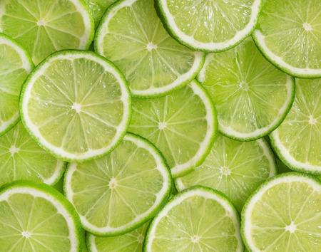 Green background with citrus-fruit of lime slices