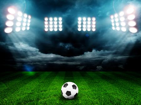 Balón de fútbol en el campo del estadio con la luz
