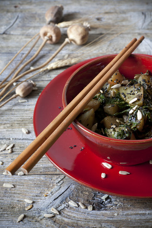 roasted japanese turnips with leaves and seeds on red bowl on rustic background  photo