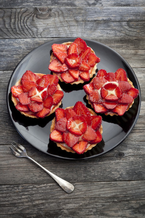 strawberries cakes franch tartellette with red fruits and pastry cream on plate with fork on wooden rustic table photo