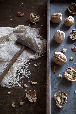 craked: craked walnuts and hammer on rustic background