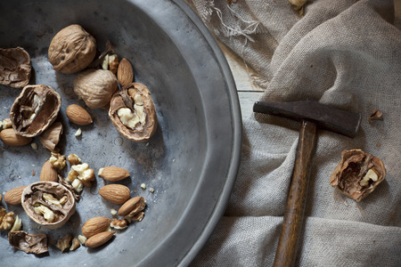 craked: craked walnuts and whole almonds with hammer on vintage plate Stock Photo