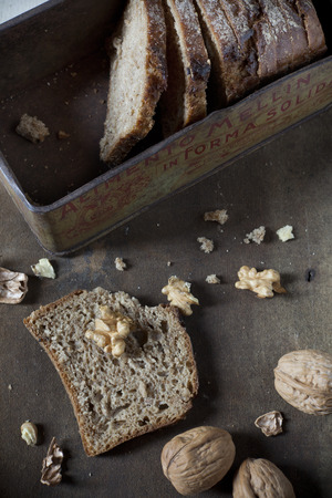 craked: natural homemade wholemeal sliced bread on vintage box with whole and cracked walnuts