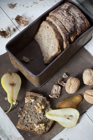 craked: natural homemade wholemeal sliced bread on vintage box with whole and cracked walnuts and slices of pear