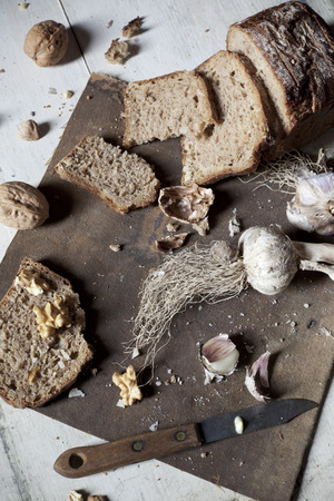 homemade wholemeal sliced bread with walnuts and whole and clove of garlic on vintage rustic background with old knife photo