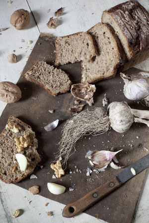 craked: homemade wholemeal sliced bread with walnuts and whole and clove of garlic on vintage rustic background with old knife Stock Photo
