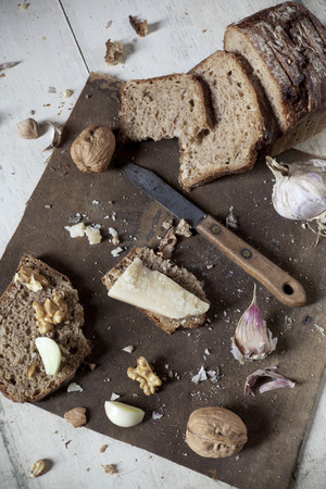 craked: homemade wholemeal sliced bread with walnuts, parmesan cheese and garlic on vintage rustic background with old knife