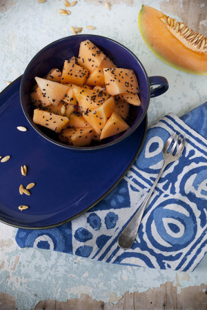 black seed: fresh pieces of melon on cup and slices with black seed on vintage background with napkin and blue plate
