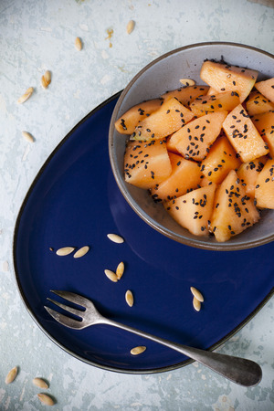 black seed: fresh pieces of melon on bowl with black seed on vintage background with napkin and blue plate Stock Photo